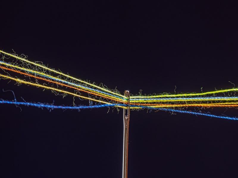 Nadel mit mehreren bunten Fäden im Nadelohr