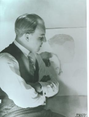Ernst Krenek, Rechtsprofil mit verschränkten Armen, dem Bild einer Frau zugewandt, in karierten Hosen, Hemd mit Krawatte und Gilet um 1920