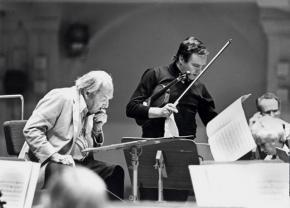 Ernst Krenek sitzend vor einer Partitur während einer Probe, rechts neben ihm der Konzertmeisters mit Geige unterm Arm, Leipzig 1980