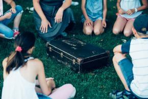 Musikvermittlung Veronika Großberger Schülerinnen und Schüler sitzen um Koffer auf Wiese, Ernst Krenek