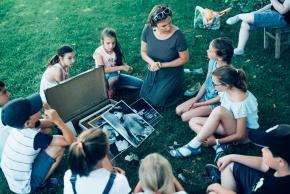 Musikvermittlung Veronika Großberger Schülerinnen und Schüler sitzen um einen Koffer auf Wiese, Ernst Krenek
