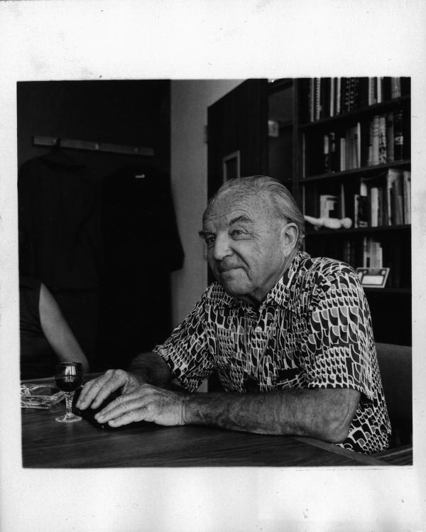 Ernst Krenek, fast Linksprofil, an einem Tisch sitzend, vor ihm ein Glas Wein, gemustertes Hemd, an der CSUN (California State University Northridge)